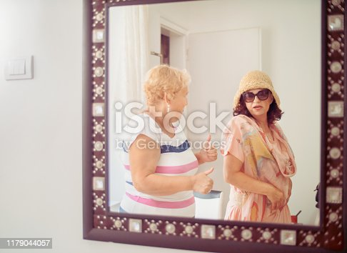 Mid adult woman showing a new dress to her girlfriend