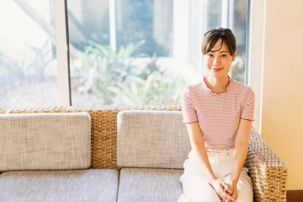 Mid adult woman sitting sofa in hotel stock photo