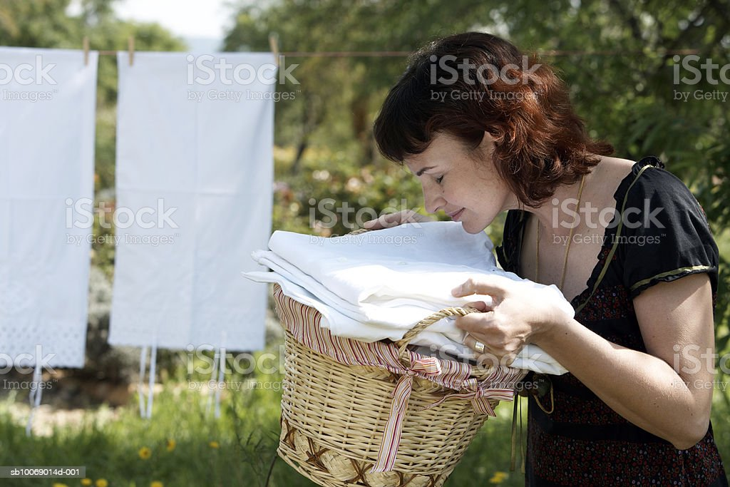 Mid adult woman smelling fleshly washed clothes in garden 免版稅 stock photo