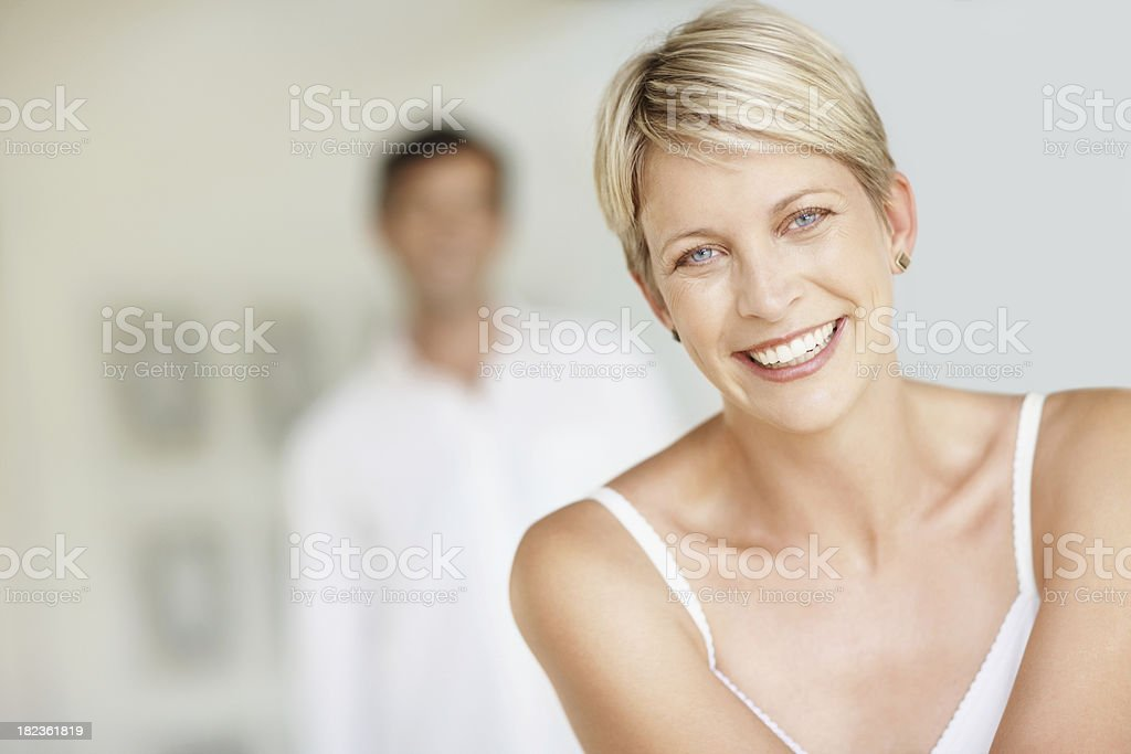 Mid adult woman smiling with husband in the background royalty-free stock photo