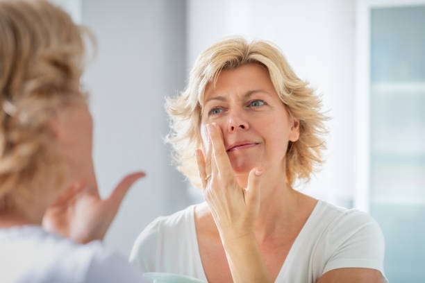 Mid adult woman spreading a layer of facial cream in front of the mirror stock photo