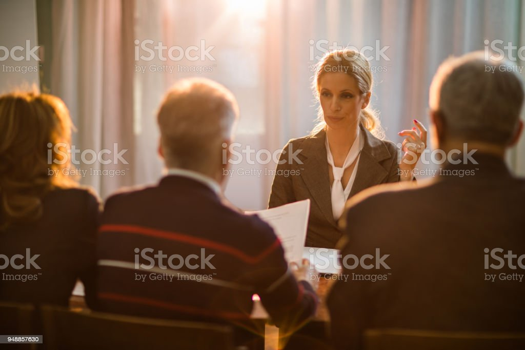 Mid adult woman talking to human resource team on a job interview. stock photo