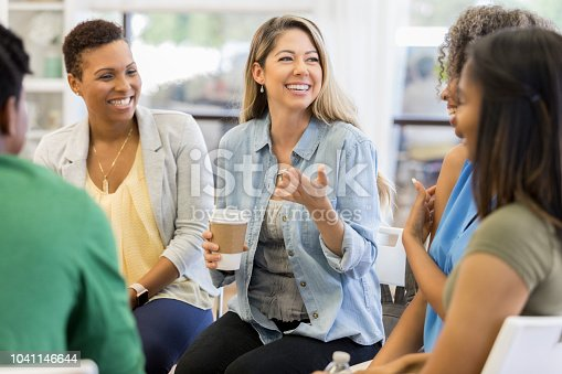 istock Mid adult woman talks during support group meeting 1041146644