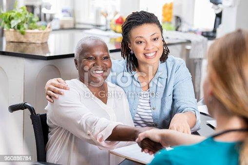 932074776 istock photo Mid adult woman talks with her mom's nurse 950886784