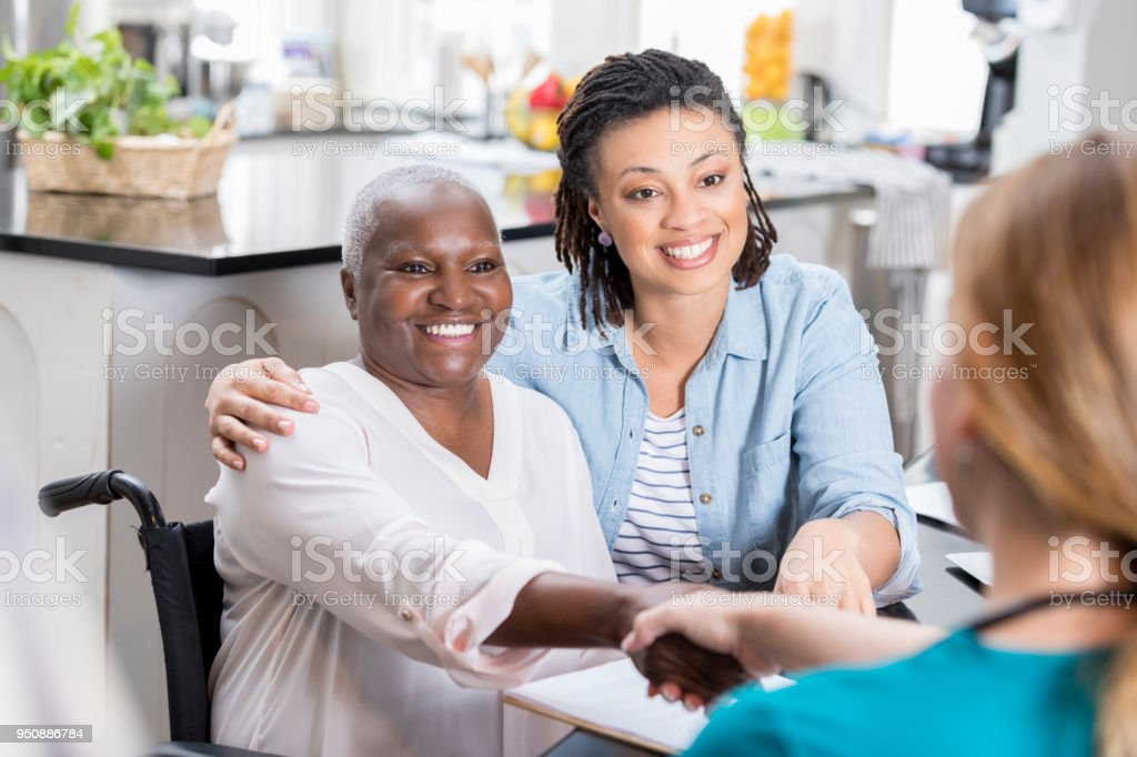 Mid adult woman talks with her mom's nurse stock photo