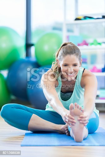 istock Mid adult woman touches toes during floor exercises at gym 821268538