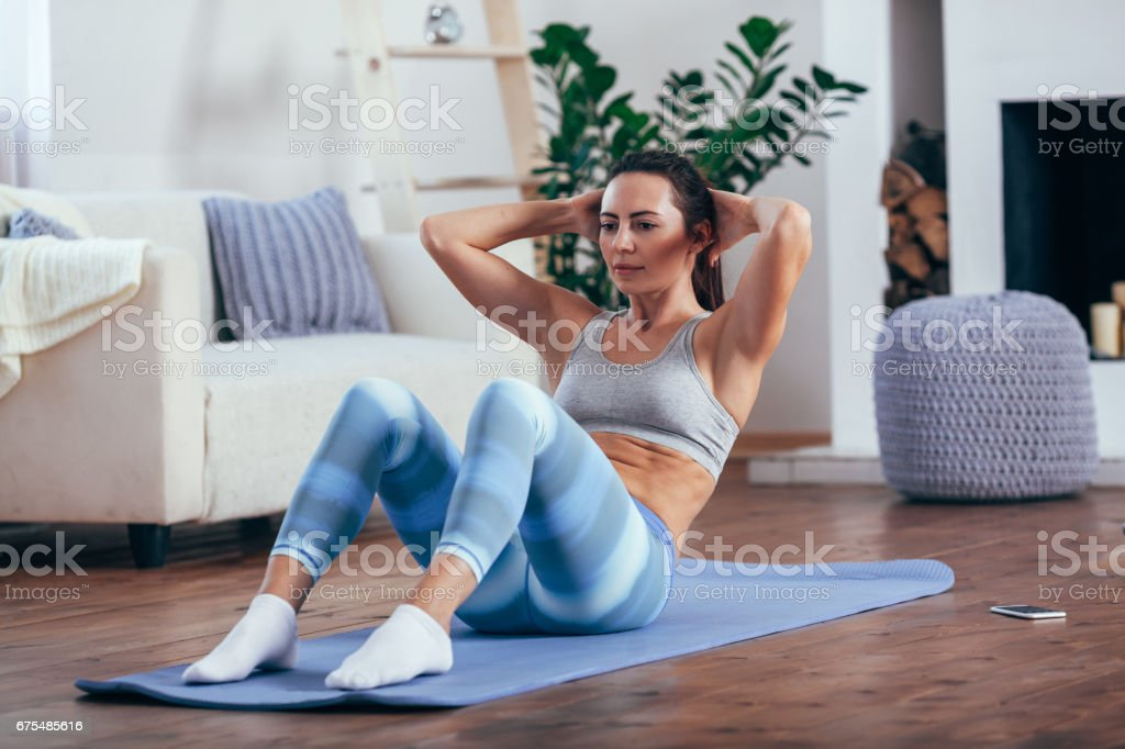 mid adult woman training abdominals at home photo libre de droits