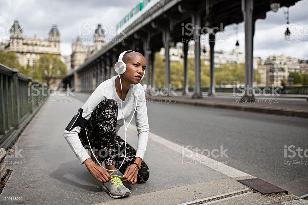 Mid adult woman tying the shoelaces before running in Paris stock photo