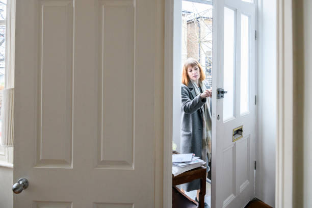 mid adult woman unlocking front door and arriving home - arrival stock photos and pictures