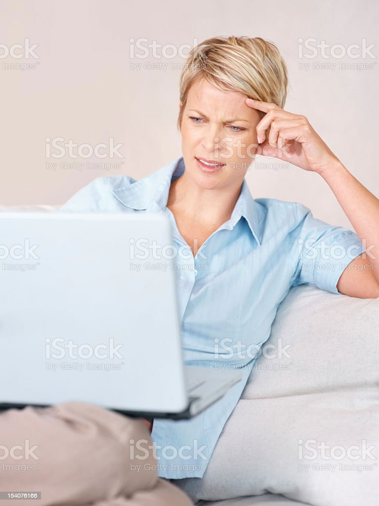 Mid adult woman using a laptop at home looking puzzled royalty-free stock photo