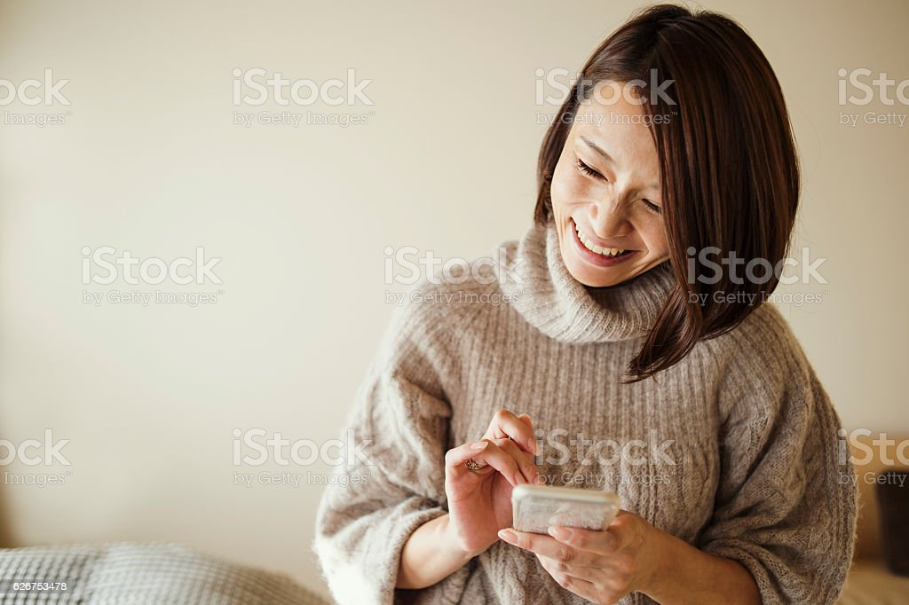 Mid adult woman using a smart phone in bed room stock photo