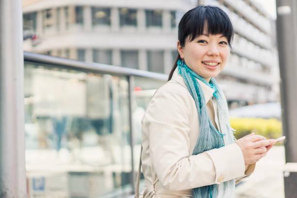 中期的成年女性在城市中使用智慧手機。 - 僅一名中年女子 個照片及圖片檔