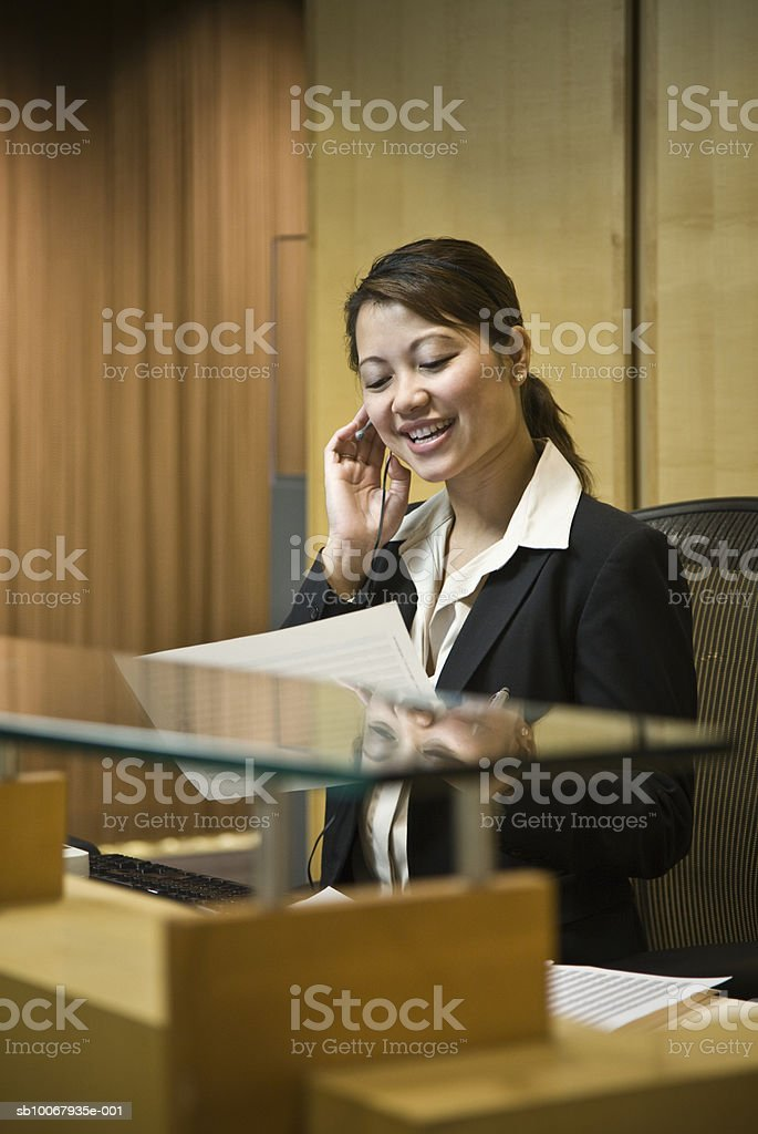 Mid adult woman using headset, holding document royalty-free 스톡 사진