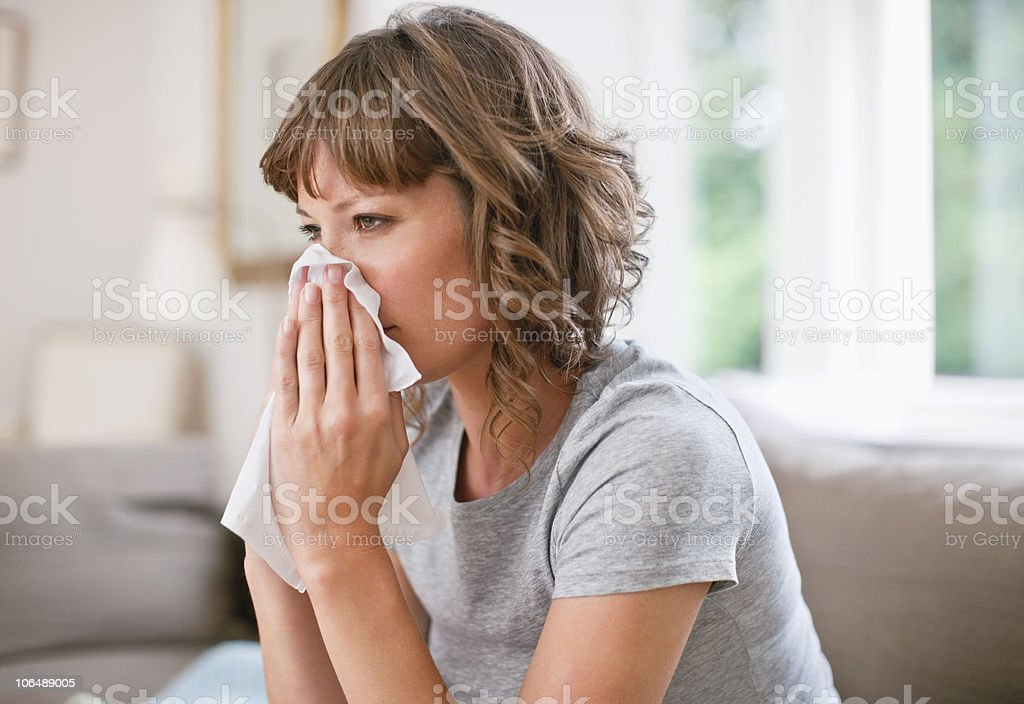 Mid adult woman using napkin for sneezing her nose royalty-free stock photo