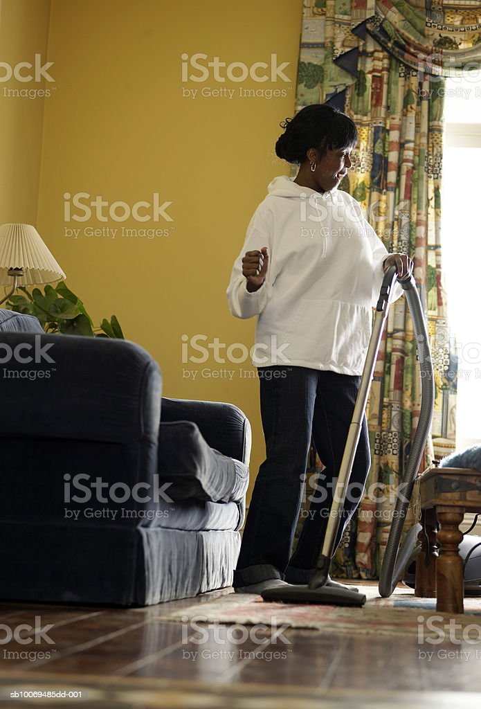 Mid adult woman vacuuming living room and watching tv royalty-free stock photo