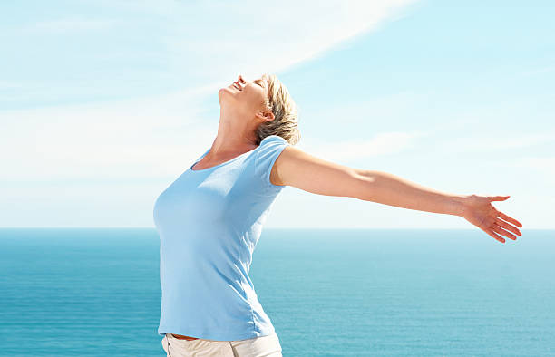 Mid adult woman with hands outstretched on a sunny day stock photo