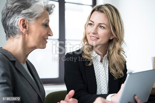 istock Mid adult woman with tablet smiling at mature colleague 519523970