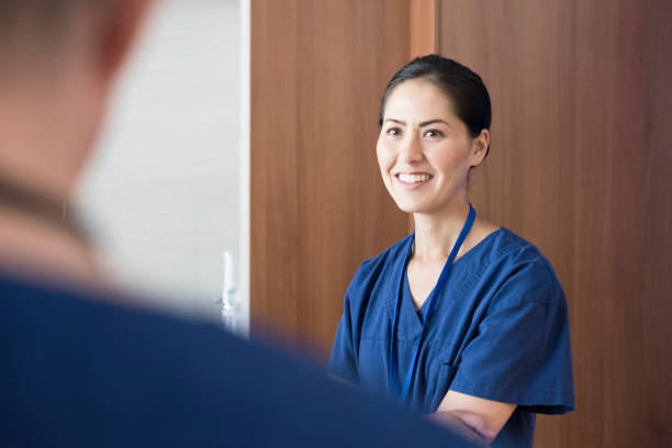 mid adult woman working in hospital smiling - australian nurses stock photos and pictures