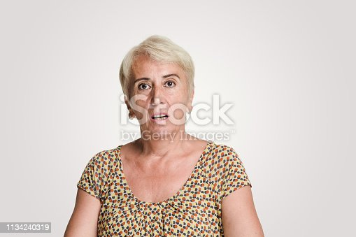 Mid adult women looking at camera with a shock expression, studio shot, white background