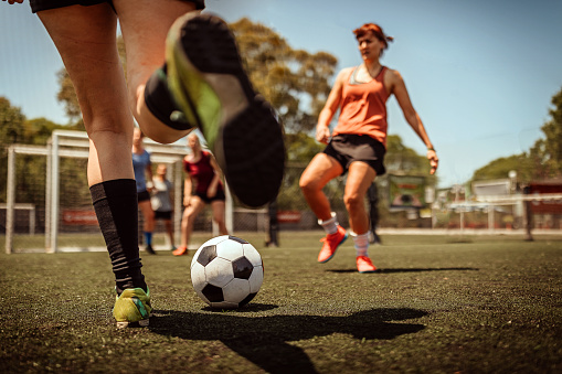 Female athlete kicking soccer ball during a match on field