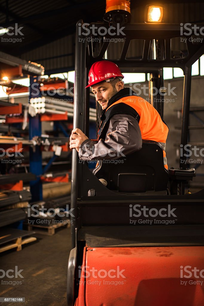 Mid adult worker driving forklift reversing in a warehouse. stock photo