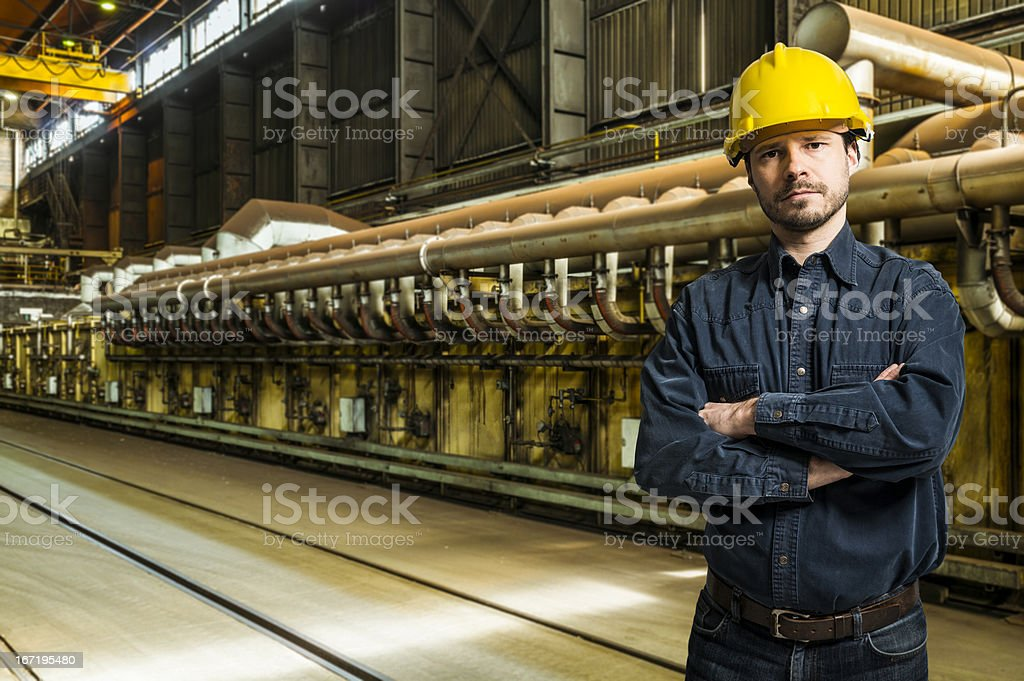 Mid Adult worker in yellow helmet inside factory interior stock photo