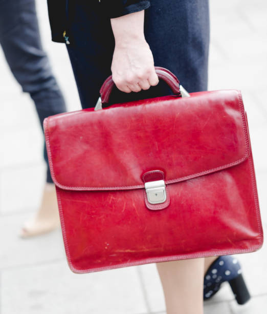 Mid age adult business woman holds red leather briefcase stock photo