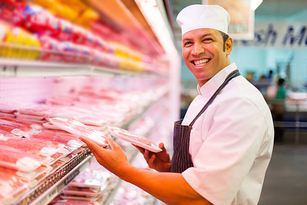 mid age butcher organizing meat products stock photo