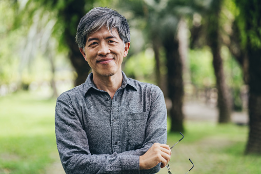 Portrait of a middle aged Chinese ethnicity man in a park