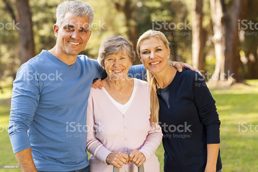 mid age couple and senior mother outdoors stock photo