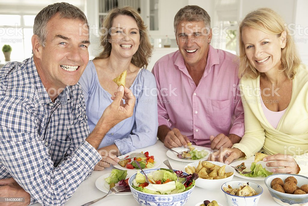 Mid age couples enjoying meal at home stock photo
