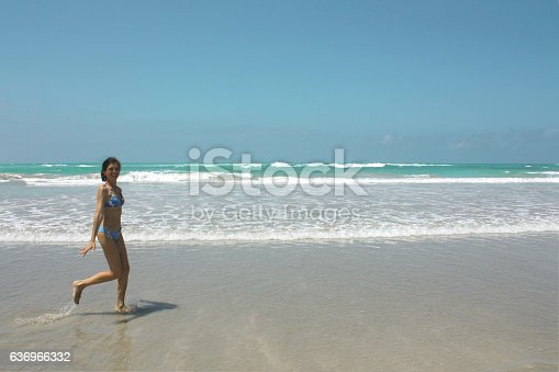 700603062istockphoto mid age Happy woman running on beach, Galapagos island 636966332
