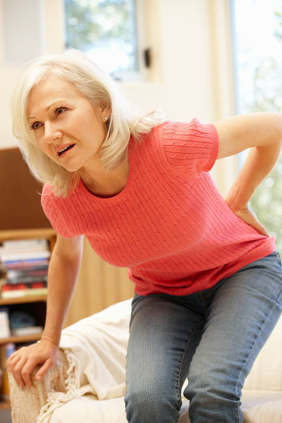 mid age woman with backache - low section stock photos and pictures