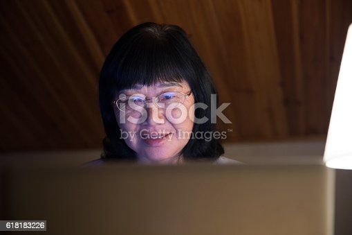 Mid age woman working at home on laptop close-up
