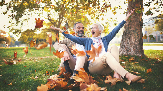 Closeup front view of early 50's couple relaxing in a park and having fun. They are sitting on the ground and throwing dry leaves.