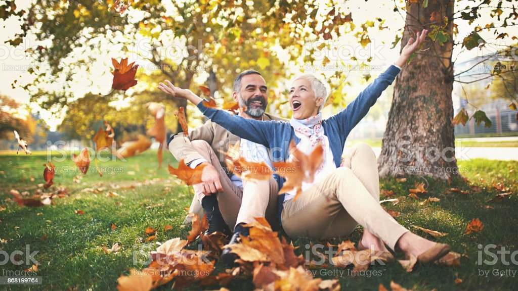 Mid aged couple having fun in a park. stock photo