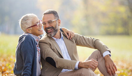 Closeup side view of a mid 50's couple sincerely enjoying their day off at a local park. They are sitting on the ground and laughing. Both wearing eyeglasses.
