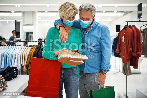 Closeup front view of a mid 50's couple going shopping after shopping malls have finally opened after coronavirus pandemic. They are wearing face masks and choosing some shoes.