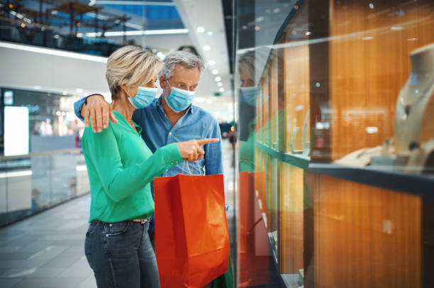 Mid aged couple in a shopping mall during coronavirus. stock photo