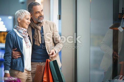 Closeup side view of an early 50's couple walking through a shopping mall and doing some window shopping. They are standing in front of home appliances store and looking at certain items they like.
