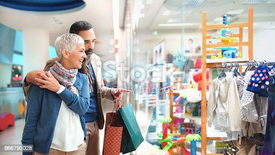 Closeup side view of a 50's couple walking through a shopping mall and looking at some clothes for their grandchildren. They are really enjoying buying for the family.