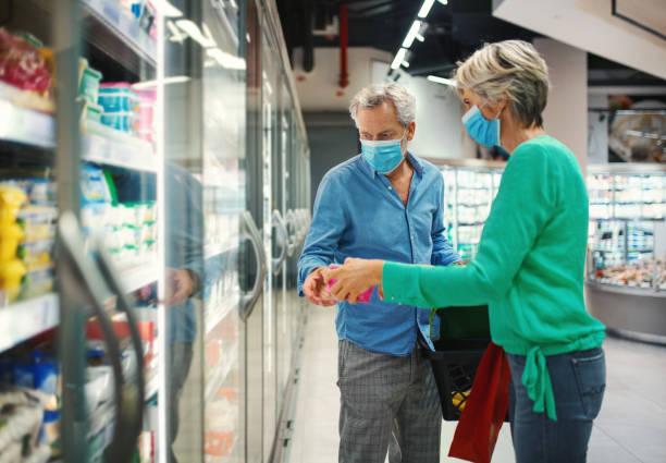 casal de meia-idade em um supermercado durante o coronavírus. - comida congelada - fotografias e filmes do acervo