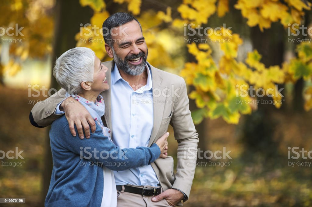 Mid aged couple walking in a park. stock photo
