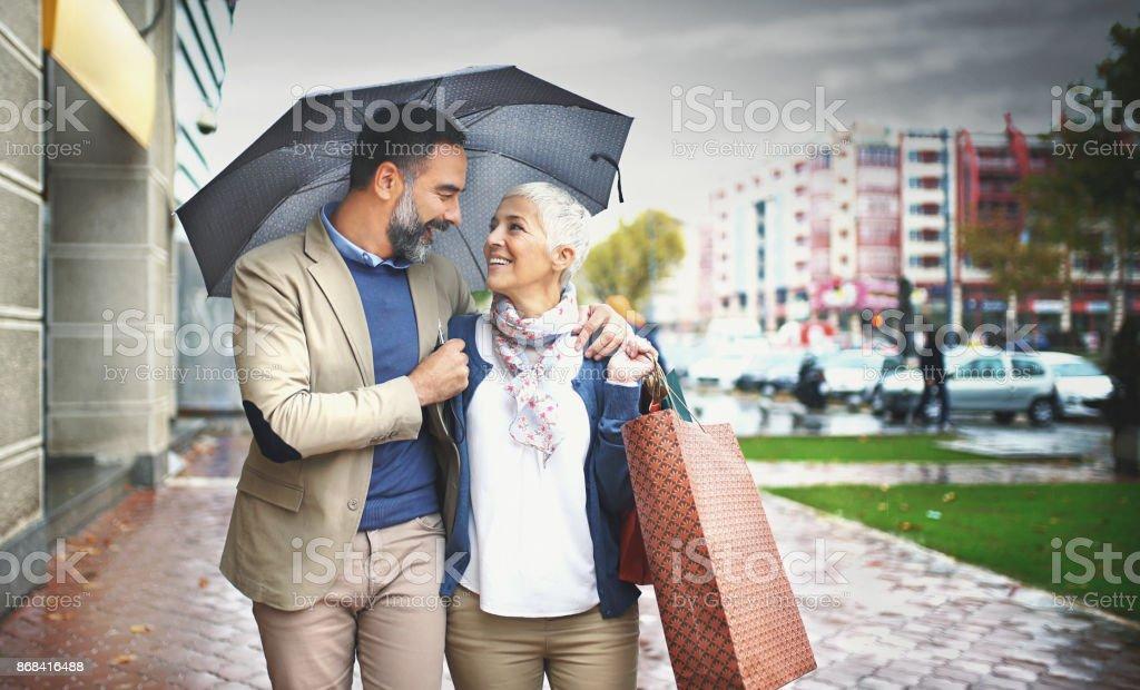 Mid aged couple walking on a rainy day. stock photo