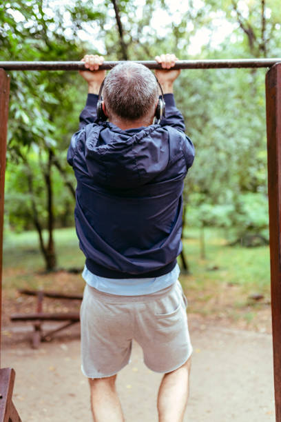 mid aged man exercising in public park - horizontal bar stock photos and pictures