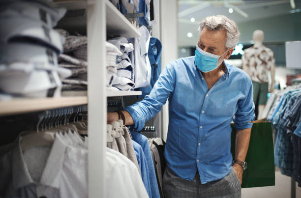 Mid aged man in buying some clothes during coronavirus. stock photo