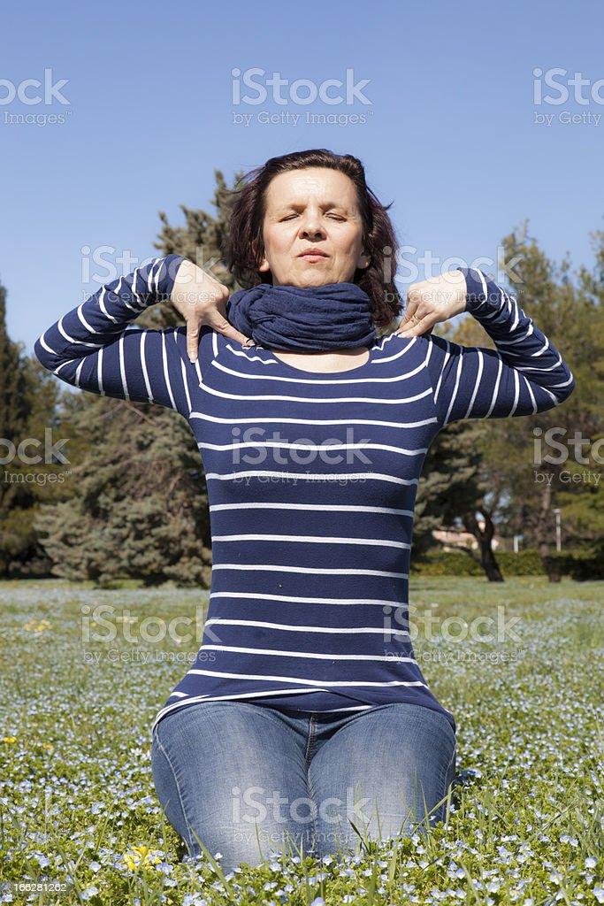 Mid aged woman doing yoga exercises outside stock photo
