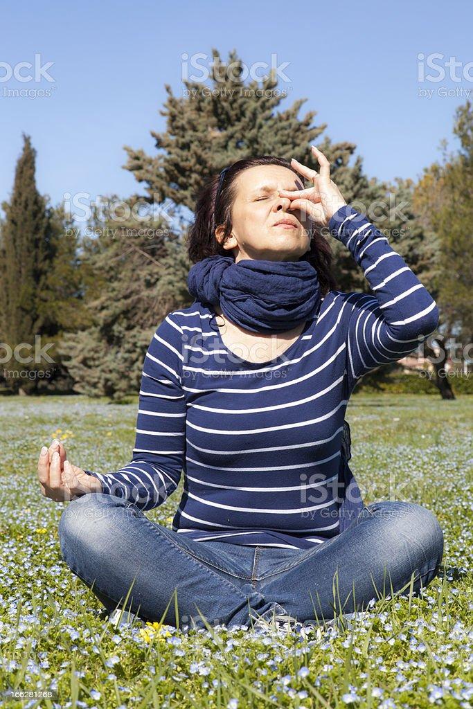 Mid aged woman doing yoga pranajama exercises outside stock photo