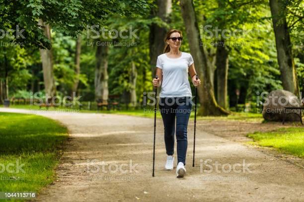 Mitte Gealterte Frau Nordic Walking Im Stadtpark Stockfoto