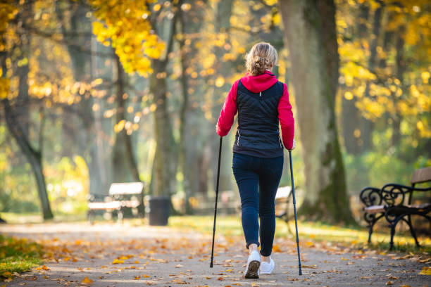 Mid aged woman nordic walking in city park People nordic walking in city park nordic walking stock pictures, royalty-free photos & images